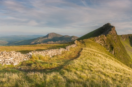 The path along the Nantlle Ridge. The path sticks to the ridge crest with vertical drops on the right to the sharp summit of Mynydd Drws-y-coed and continues towards the right edge of the shot. In the distance on the left is Moel Hebog.